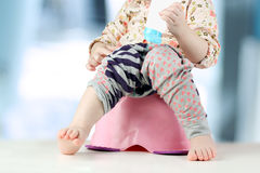 Children's legs hanging down from a chamber-pot on a blue backgr Royalty Free Stock Image