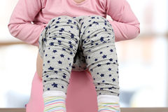 Children`s legs hanging down from a chamber-pot on a pink background stock images
