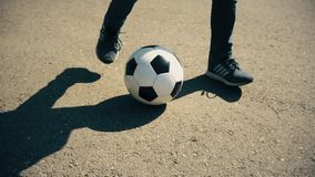 Children`s legs play with a soccerball on the road stock video