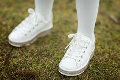 Children`s legs in white sneakers standing on the green grass outdoor royalty free stock photo