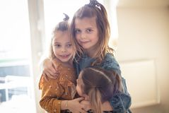 Children`s love is the most pure. Three little girls at home royalty free stock photos