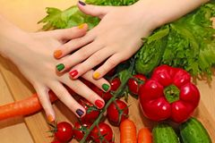 Children`s manicure with colorful nail Polish design. Children`s manicure with colorful nail Polish design for your nails on the girl with different foods Royalty Free Stock Photos