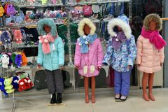 Children's mannequins in winter down jackets in the store stock photo