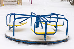 Children`s merry-go-round covered in snow on playground in winter Royalty Free Stock Image