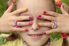 Children`s multicolored manicure. Children`s multicolored manicure with stripes on a light girl with rubber bands on a summer day Royalty Free Stock Photo