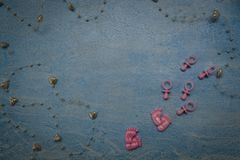 Children`s nipples of the heart and small feet feet on a blue background Royalty Free Stock Photography