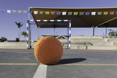 Children`s orange rubber soccer ball front of gates. On the court Royalty Free Stock Images