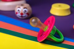 Children`s pacifier with a colored wooden clown on colored paper royalty free stock photos