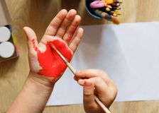 Children`s painted hands. Children`s hands and palms are painted with colored paint. Joy, the school concept. stock image