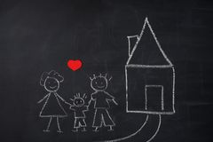 Children`s painting on chalkboard. family and new home. Stock Photo