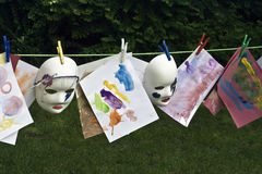 Childrens paintings. A line of childrens paintings and masks hanging on a line to dry stock image