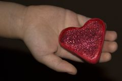 Children`s palm offers a toy of plasticine - the heart. royalty free stock photos
