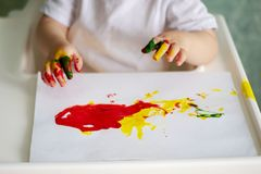 The children`s palms, soiled with paint, amuse the child stock image