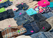 Children`s pants on display at a suburban garage sale. Boy`s pants with price tags on a garage sale table Royalty Free Stock Photo
