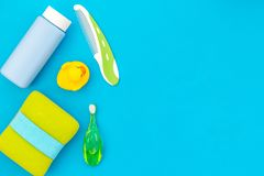 Children`s personal care kit. Bath accessories with teeth brush and yellow rubber duck on blue background top view space stock photography