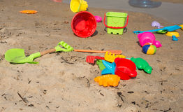 Children's plastic toys scattered on the beach Stock Photos