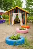 Children`s play house on sand playground with flower bed.  stock photography