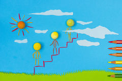 Children's play: Social ladder. Figurative person climbing to the sky on a sunny day with green grass and blue sky Royalty Free Stock Images