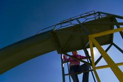 Children's play-structure; a slide. Low-angled shot of a children's play-structure - a slide - shot against blue sky and bright sun Stock Images