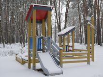 Children`s Playground in the forest covered with snow stock image