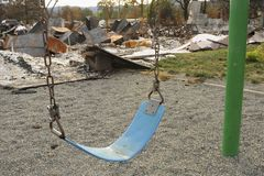 Children`s playground destruction caused the Valley Fire during the 2015 California wildfire season in Lake County. Behind an aging child`s swing, charred royalty free stock image