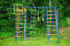Children`s Playground in the nature, outdoors. Children`s sports equipment, ladder, horizontal bar, gymnastic rings Stock Images