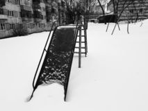 Childrens playground near the house in winter. In the snow royalty free stock photography