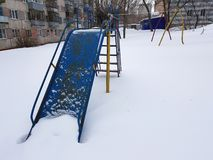 Childrens playground near the house in winter. In the snow stock images
