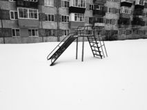 Childrens playground near the house in winter. In the snow stock image