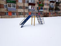 Childrens playground near the house in winter. In the snow stock photography