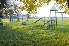 Children's playground near the stadium on the background of sunset. Swings, slide and ladder. Carousel and shop. Leisure for chil Royalty Free Stock Images