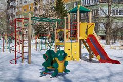 A children`s Playground with a slide, a ladder, swings, a rope and a frog rocking chair. New play complex for children in the yard. Winter Sunny day, white Royalty Free Stock Photo