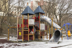 Children`s playground with slide outdoors winter season. On cloudy day Stock Images