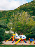 Children`s playground with slides and swings. Children`s slide i. N the form of an airplane. Park Sveti Stefan, Montenegro Stock Photos