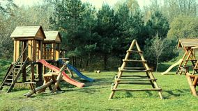 Children`s playground in summer with swings and slides, made of wooden beams. Children`s playground in summer with swings and slides, made entirely of wooden stock footage