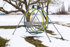 Children`s playground in winter under snow. Swing, carousel and slide. Winter desolation.  Royalty Free Stock Images