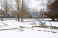 Children`s playground in winter under snow. Swing, carousel and slide. Winter desolation.  Royalty Free Stock Photos