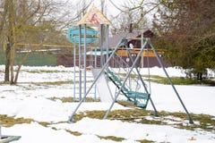 Children`s playground in winter under snow. Swing, carousel and slide. Winter desolation.  Stock Image