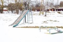 Children`s playground in winter under snow. Swing, carousel and slide. Winter desolation.  Stock Photos