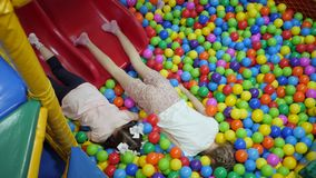Children`s playroom. Children play in a dry basin filled with plastic colored balls. stock footage