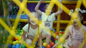 Children`s playroom. Children play in a dry basin filled with plastic colored balls. stock video footage