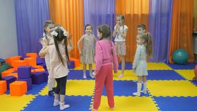 Children`s playroom. Studio entertainment for young children. Children are standing in a circle and playing ladushki stock video footage