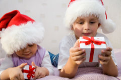 Children's pleasure. Two small children lie on a sofa and consider the gifts Stock Image