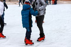 Children`s rink. The instructor teaches the teenager boy to skate. Active family sport during the winter holidays. Children`s rink. The instructor teaches the stock image