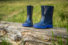 Children`s rubber boots on a log Stock Image