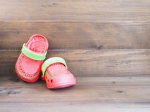 Children`s rubber sandals on wooden background Stock Photography