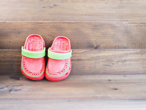 Children`s rubber sandals on wooden background Stock Image