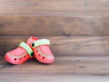 Children`s rubber sandals on wooden background Royalty Free Stock Image