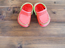 Children`s rubber sandals on wooden background Royalty Free Stock Photography