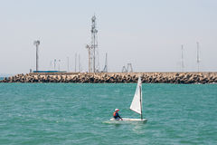 Children's sailing yacht and lighthouse in Pomorie. Bulgaria. Pomorie - ancient Bulgarian seaside town famous discoveries of ancient Slavic settlements. Located Stock Photography